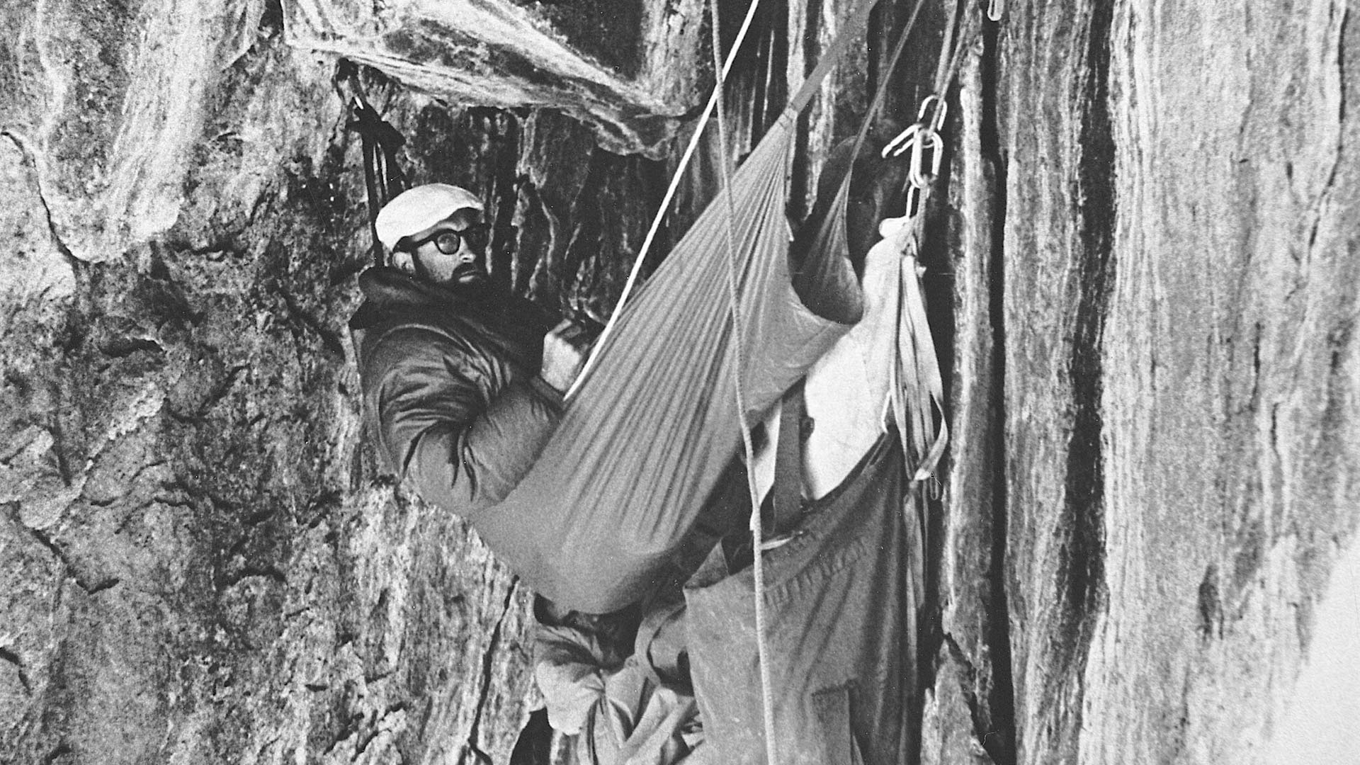 Royal Robbins and Yvon Chouinard (peeking out of the bottom), bivouacking in The Black Cave during the first ascent of the North America Wall, El Capitan, Yosemite, California. 1964. CHUCK PRATT