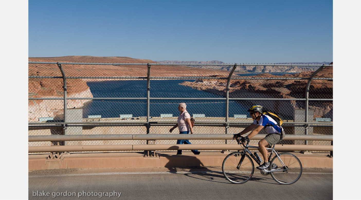 Lin Alder crosses the Glen Canyon Dam bridge on the opening day of the Lake Powell Pipeline Trek. Alder and Scott Hirschi went on an 8 day trek along the route of the proposed Lake Powell Pipeline to generate community discussion. Photo: Blake Gordon.