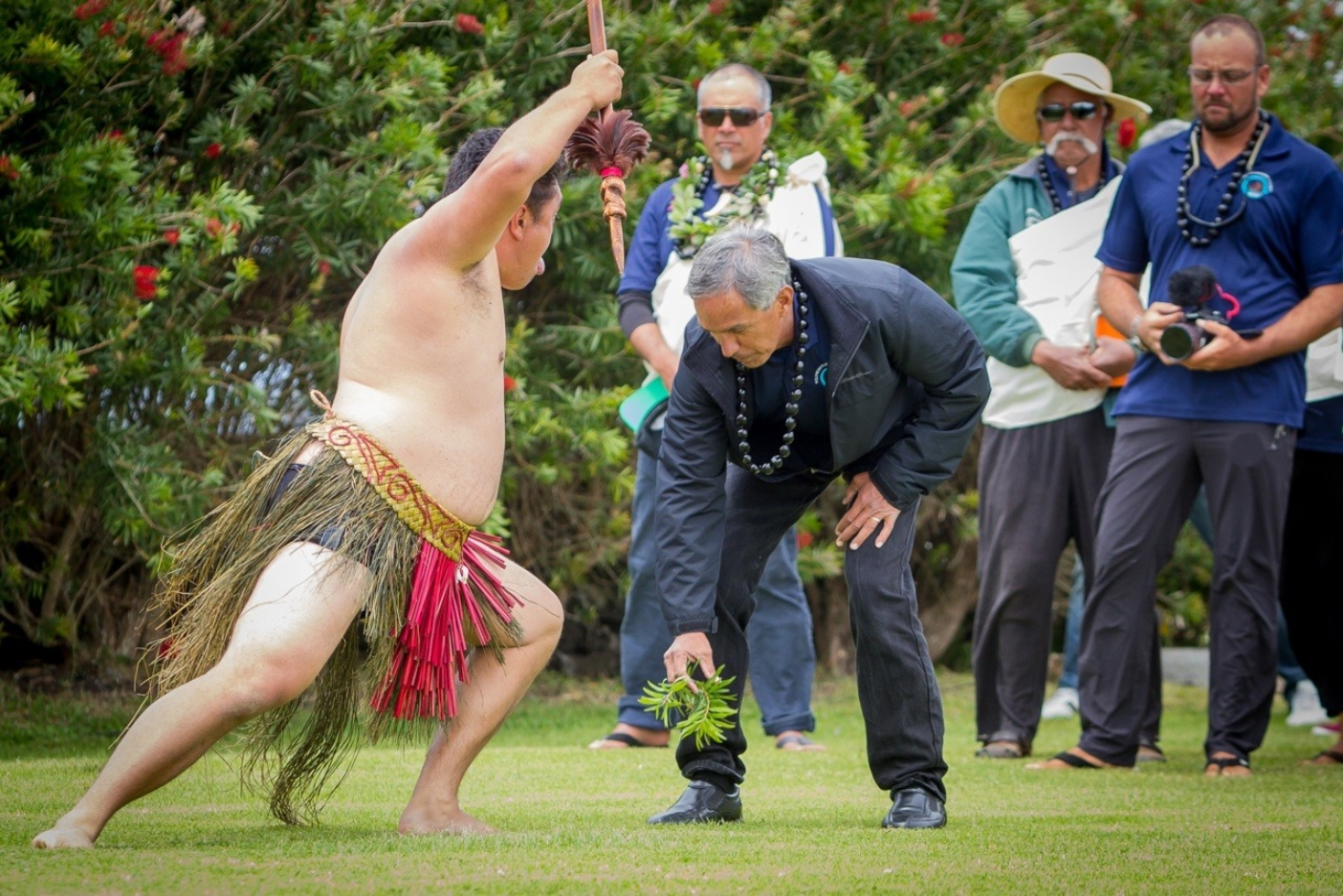 Once the crew has come ashore, the haka begins. A Māori has placed a branch on the grass as a challenge to the Hawaiian visitors. Captain Nainoa Thompson collects it, unflinchingly, as a warrior advances. Photo: John Bilderback