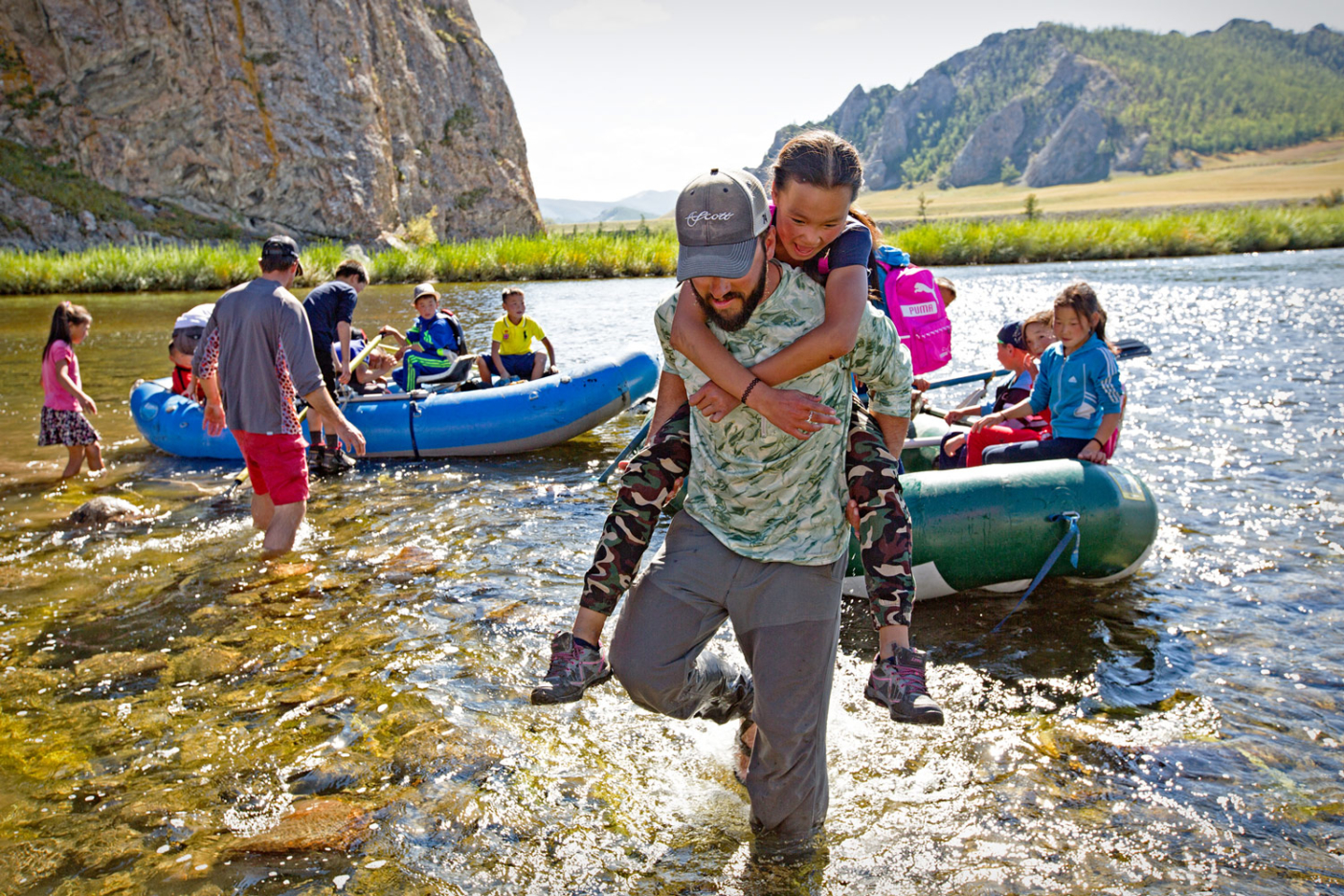 Jeff Forsee, head guide of Fish Mongolia, helps a young local girl to shore for a fly fishing lesson. Photo: Earl Harper