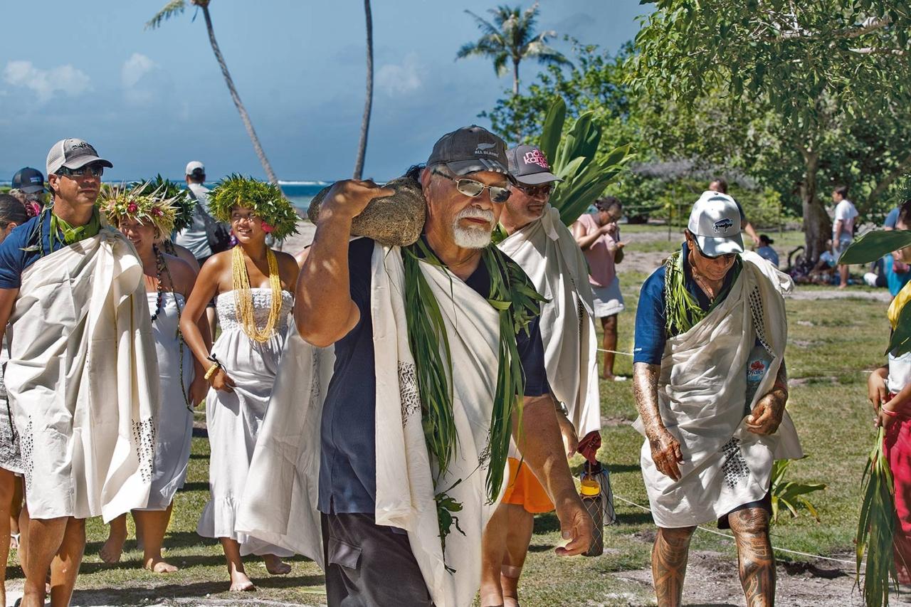 John Kruse, who helped build Nāmāhoe, a seventy-two-foot double hull voyaging canoe from the island of Kaua'i, bears a pōhaku at Taputapuātea. Photo: John Bilderback