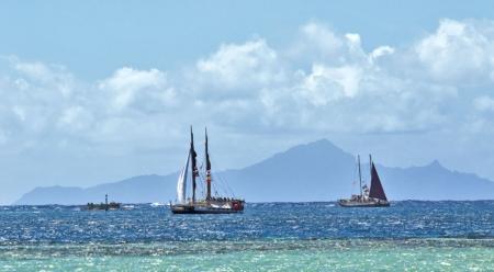 With the wind in the high twenties and minimal sail up, Hōkūle'a and Hikianalia sail into Te Ava Mo'a, the Sacred Pass to Taputapuātea. Photo: John Bilderback