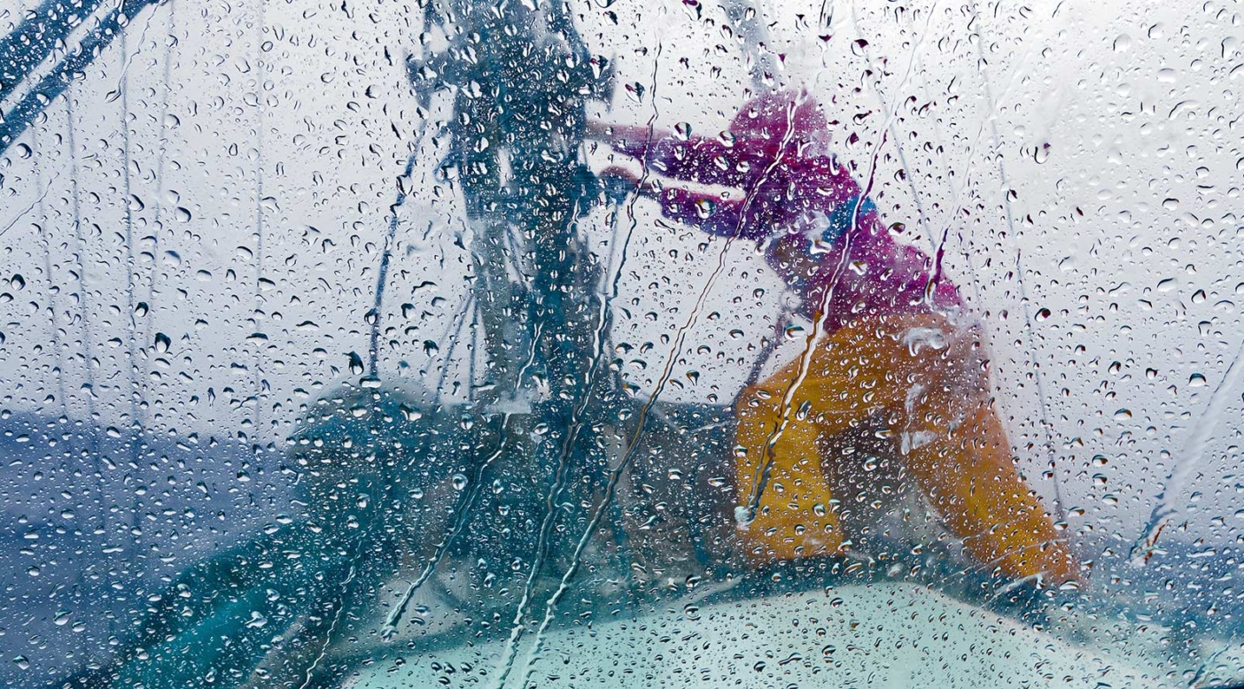Caught by the heavy winds of a fast-moving South Pacific squall, Liz Clark heads to the mast to put another reef in Swell's sail. Photo: Tahui Tufaimea
