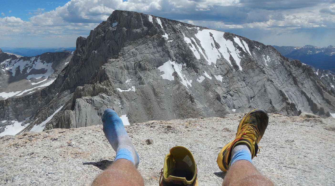 Emptying rocks from the shoes atop Mt. Russell, with a view a Mt. Whitney. Photo: Erik Schulte