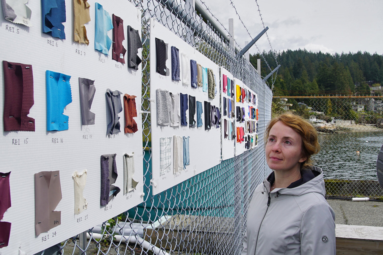 """Katerina Vassilenko from Ocean Wise's Plastic Lab stands next to fabric swatches tested in the weathering experiment. """"We want to know where, exactly, the microfibers that we find come from. The better we understand it, the more effectively we can act to reduce it,"""" she said. Photo: Lorand Szasz (Ocean Wise/Vancouver Aquarium)"""