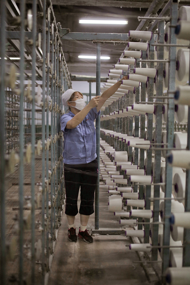 Smaller spools of processed hemp fiber now feed the giant loom to create bolts of yarn prior to weaving. Photo: Lloyd Belcher