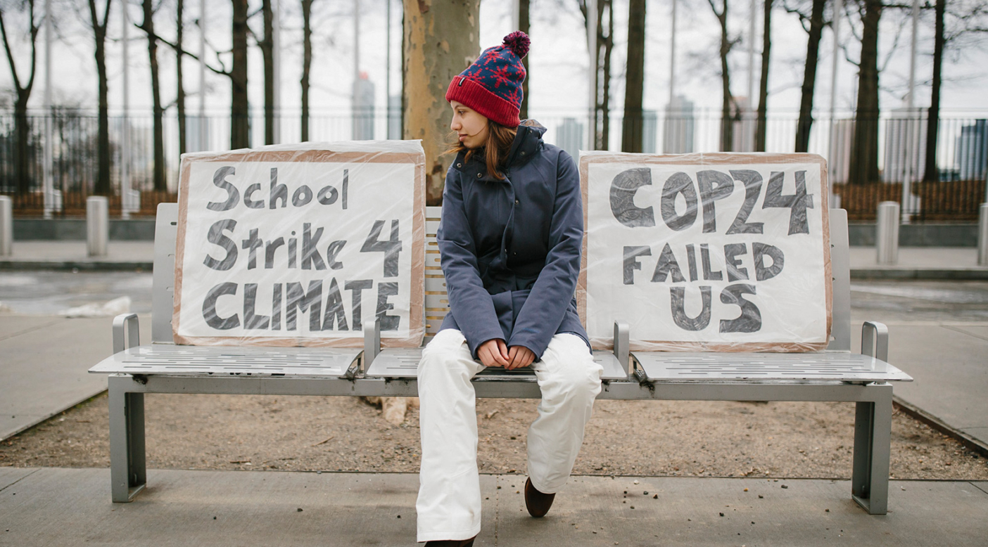 "Alexandria started striking against climate inaction on December 14, 2018. She was inspired by Greta Thunberg's Friday protests in front of the Swedish Parliament. She usually sits on this bench nearby the UN Headquarters in New York City with her two signs. ""Most people pass me by, but some stop and ask me to tell them about my signs. One Swedish girl saw me one day and said she knew Greta and the student strike movement. We took a photo and she cried."" Photo: Joel Caldwell"