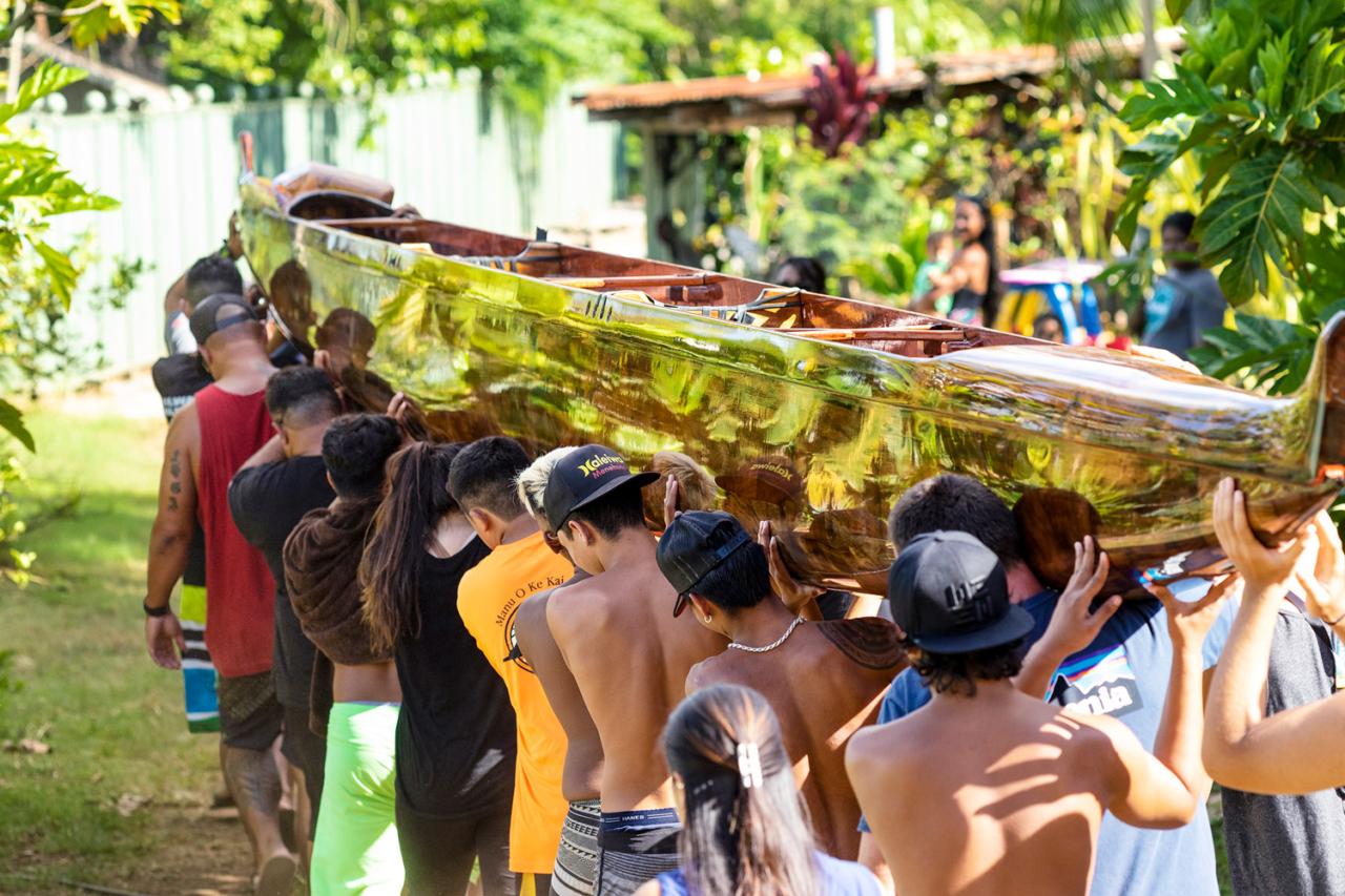 With work complete and U'i all shined up, members of the Manu O Ke Kai Canoe Club hoist her on their shoulders as they head for the O'ahu outrigger championships. Hale'iwa, Hawai'i. Photo: John Bilderback
