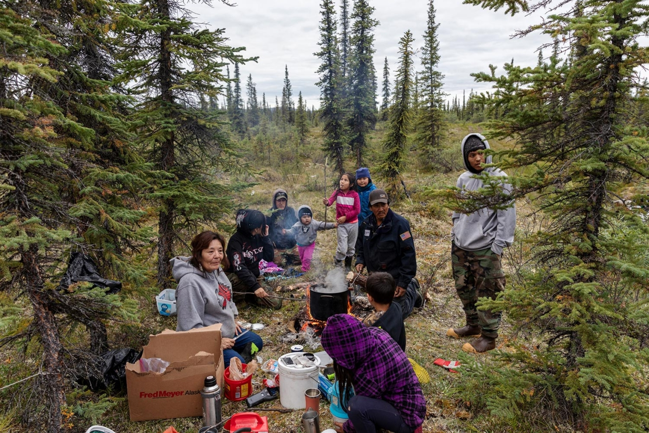 Traditions like hunting and gathering are as important as protecting the land for the Gwich'in. Here, the Gilbert family and friends take a break from picking berries to eat moose soup cooked over a fire, the preferred cooking method when cooking traditional foods. Photo: Keri Oberly
