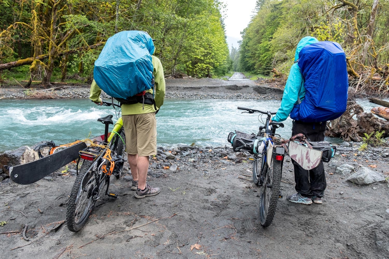 Wild rivers will do wild things. Marie-France Roy and Kael Martin contemplate a major road blow-out along the Elwha River and potential end to the bike-assisted portion of their approach to Mount Olympus.  Photo: Colin Wiseman