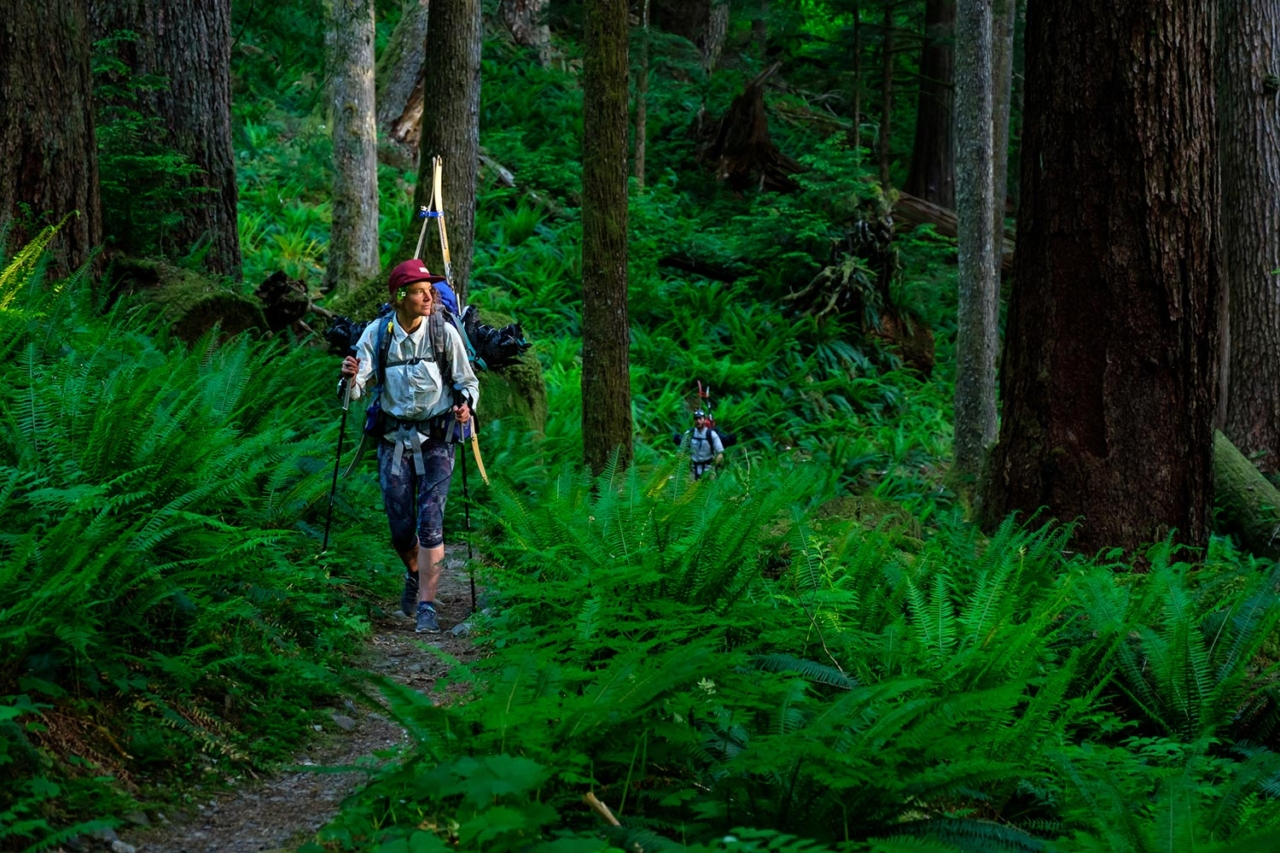 Marie-France Roy and Kael Martin descend along the upper reaches of the Hoh River Trail seven days into an eight-day traverse through the Olympic Mountains. We'd finally swapped soggy snowboard boots  for dry shoes, and as we walked through the rainforest,  the sunset bathed the old-growth with golden light. Photo: Colin Wiseman