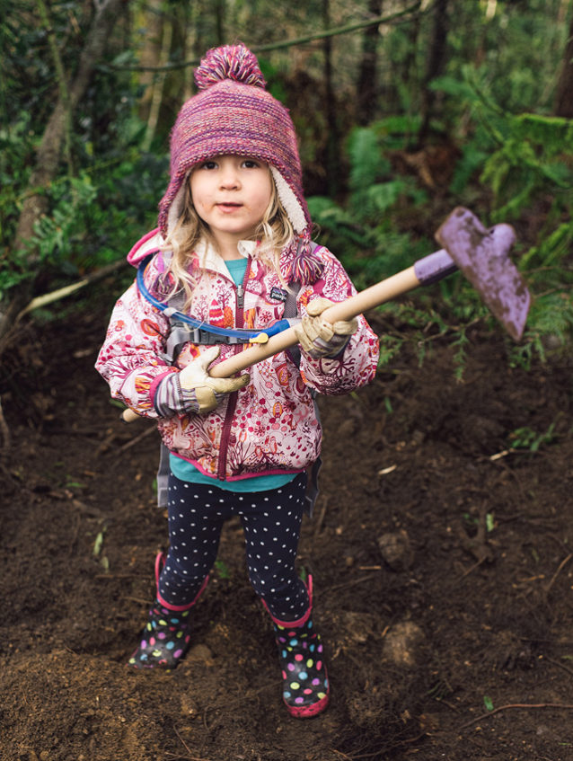 Teach 'em young. Wielding her own purple-painted hoe and rubber boots, Cloe Brown helps her dad during a trail day on Galbraith. The bimonthly work parties regularly draw dozens of volunteers, including families and riders of all ages. Photo: Paris Gore
