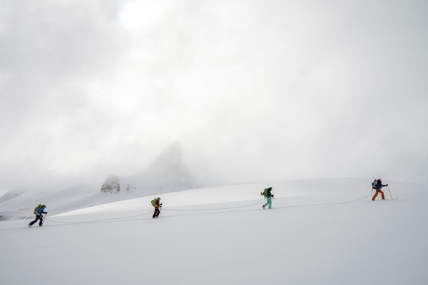 "Cresting toward a high pass on the Bow Glacier, the team traverses below the iconic Saint Nicholas Peak. After several stormy days, the clouds were just beginning to recede, the mountains shed their shrouds, and we knew that our young ""powderhounds"" would soon be sniffing out worthy ski lines. Photo: Kennan Harvey"