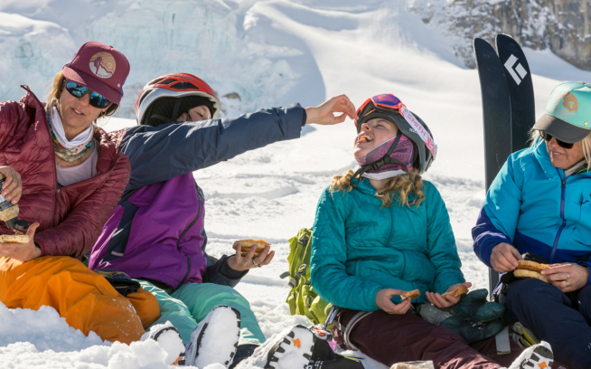 During a mountain gourmet lunch stop—meat, cheese, week-old bagels and stone-ground mustard—Nan Cresto, her daughter Sailor Kabeary, Roan Harvey and Cheryl Albrecht-Harvey recharge after a morning of multiple low-angle powder laps during a rest day outing above the Peyto Hut.   Photo: Kennan Harvey