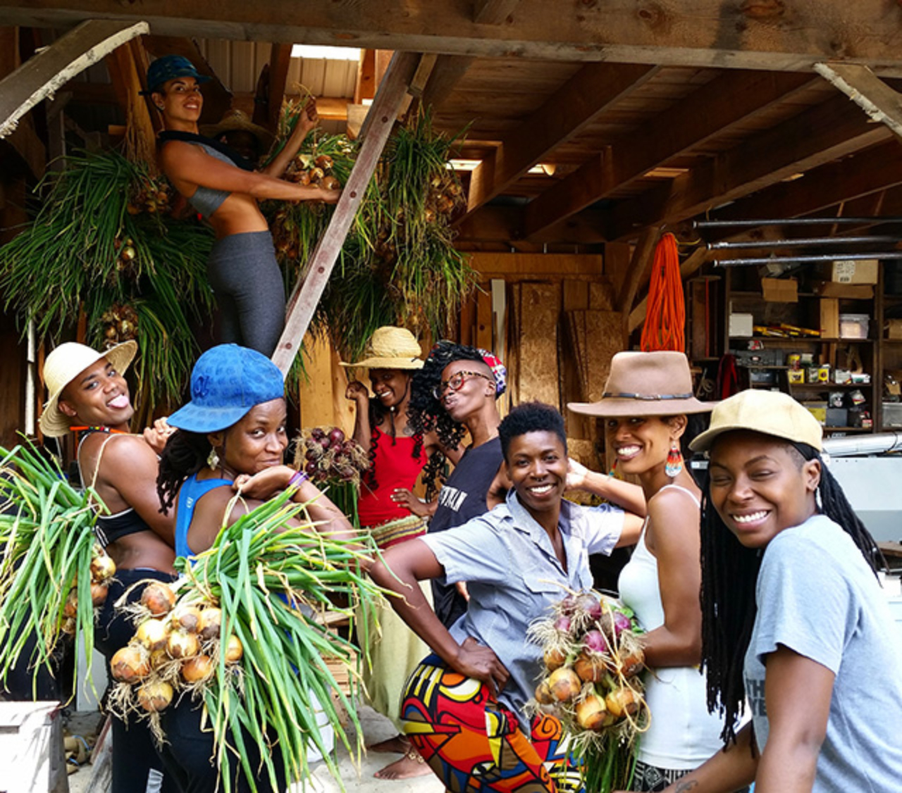 Black Latinx Farmers Immersion participants hanging onions to cure in the barn. Photo: Leah Penniman
