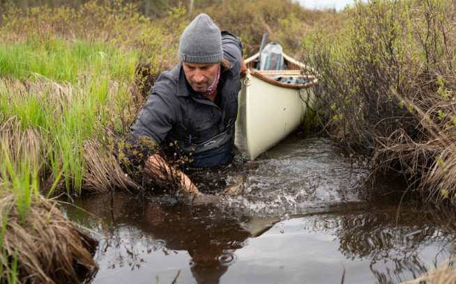 Boots in the water and paddle on the bow seat, Nathaniel Riverhorse Nakadate navigates a tight, soggy portage. TONY CZECH