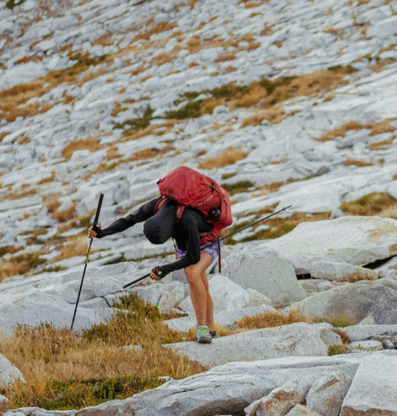 Jenn Shelton completing the Sierra High Route. Shelton is hiking over rocky terrain, doubled over as if from exhaustion.